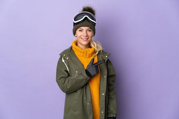 Esquiadora russa com óculos de snowboard isolados em um fundo roxo apontando para o lado para apresentar um produto