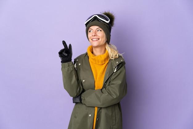 Esquiadora russa com óculos de snowboard isolados em um fundo roxo apontando para uma ótima ideia