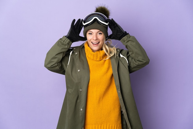 Esquiadora russa com óculos de snowboard isolados em um fundo roxo com expressão de surpresa