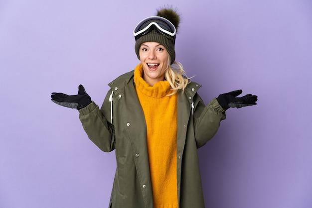 Esquiadora russa com óculos de snowboard isolados em um fundo roxo com expressão facial chocada
