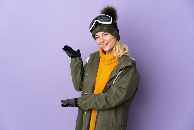 Esquiadora russa com óculos de snowboard isolados em um fundo roxo estendendo as mãos para o lado para convidar a vir