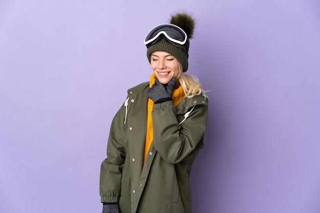 Esquiadora russa com óculos de snowboard isolados em um fundo roxo, olhando para o lado e sorrindo