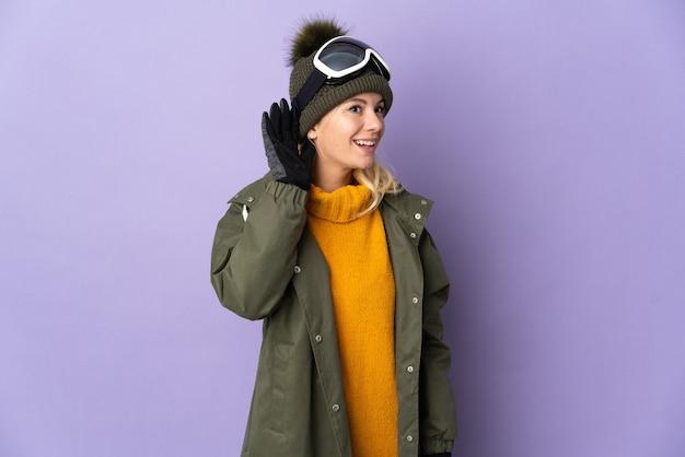 Esquiadora russa com óculos de snowboard isolados em um fundo roxo ouvindo algo colocando a mão na orelha
