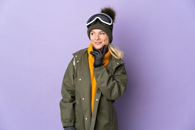Esquiadora russa com óculos de snowboard isolados em um fundo roxo pensando uma ideia enquanto olha para cima