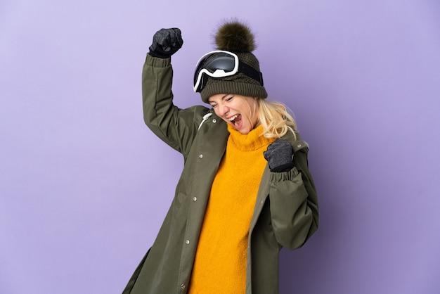 Esquiadora russa com óculos de snowboard isolados na parede roxa comemorando uma vitória