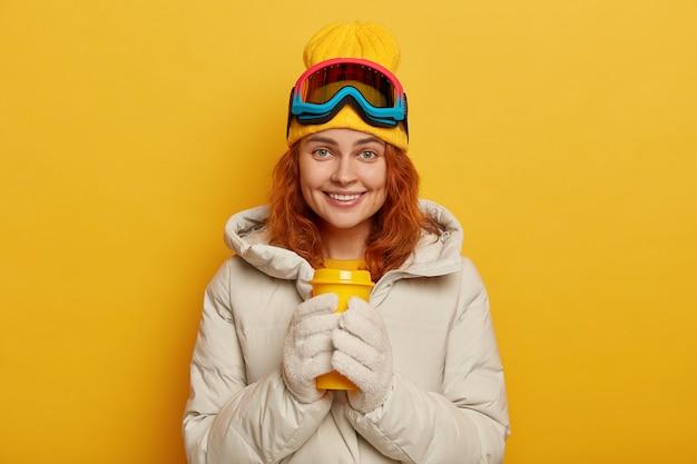 Esquiadora usa agasalhos de inverno quentes, segura uma xícara amarela para viagem com chá quente, usa boné e óculos de esqui, sorri agradavelmente, modelos dentro de casa.