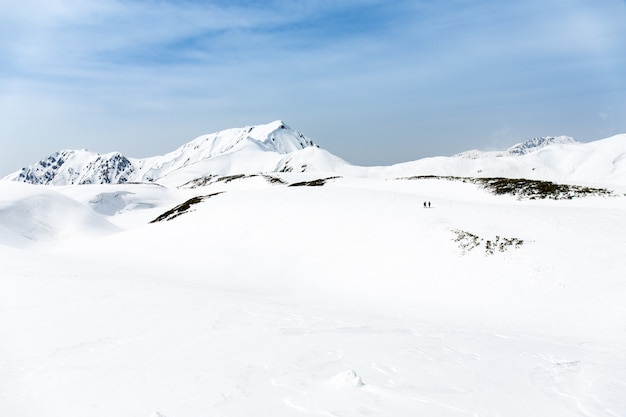 Esquiadores andando na neve cobriu cordilheiras
