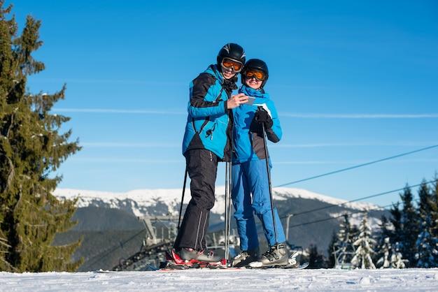 Esquiadores de casal em pé no topo da montanha em dia ensolarado de inverno