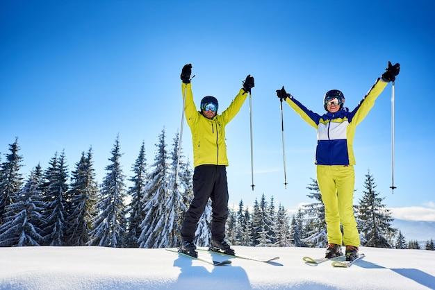 Esquiadores de casal feliz em pé na borda da montanha, regozijando-se, levantando as mãos. céu azul claro sobre a natureza da montanha de inverno.