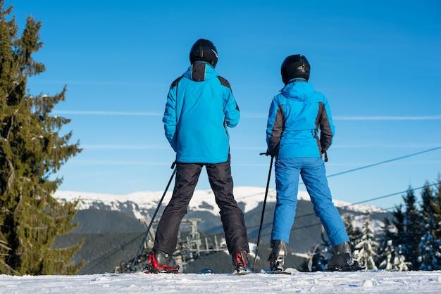 Esquiadores de homem e mulher em pé no topo da montanha juntos, apreciando a bela paisagem de montanha em um resort de inverno em dia de sol