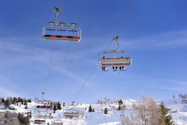 Esquiadores em um elevador de esqui no resort europeu alpino