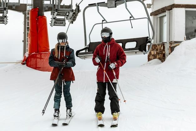 Esquiadores full shot perto do teleférico