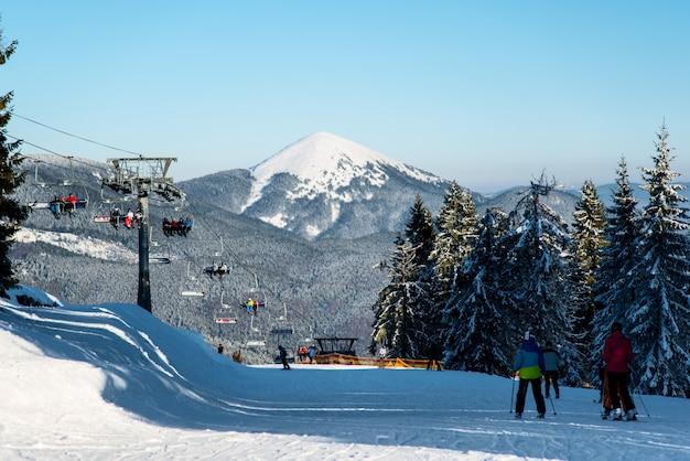 Esquiadores na estação de esqui, elevador, florestas, colinas
