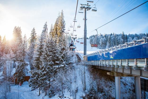 Esquiadores no teleférico subindo no resort de esqui com belas florestas