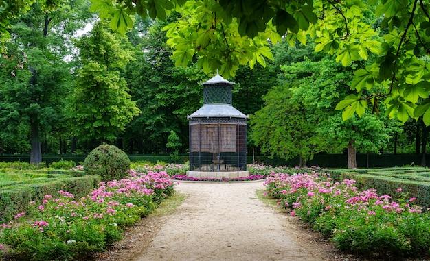 Esquina do parque público com uma grande gaiola de pássaros e sebes floridas na primavera