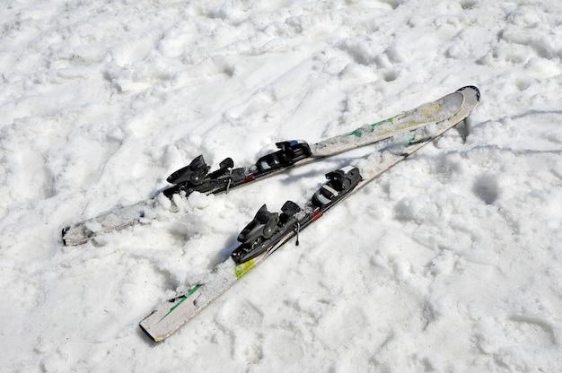 Esquis abandonados na neve. vista do topo. conceito de fim de temporada de esqui.