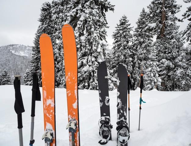 Esquis de montanha, splitboard e bastões na neve. equipamento de esqui de fundo