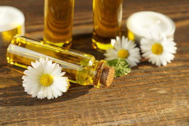 Essência de flores e ervas em um frasco de vidro bonito na madeira