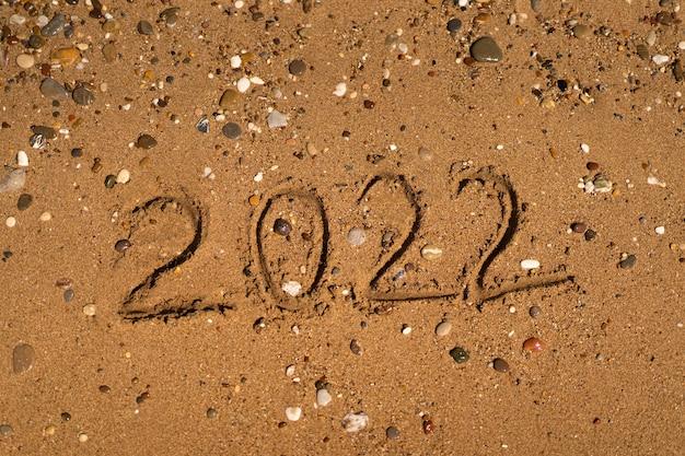 Está desenhando na areia de uma praia com uma onda à beira-mar férias no mar conceito de ano novo