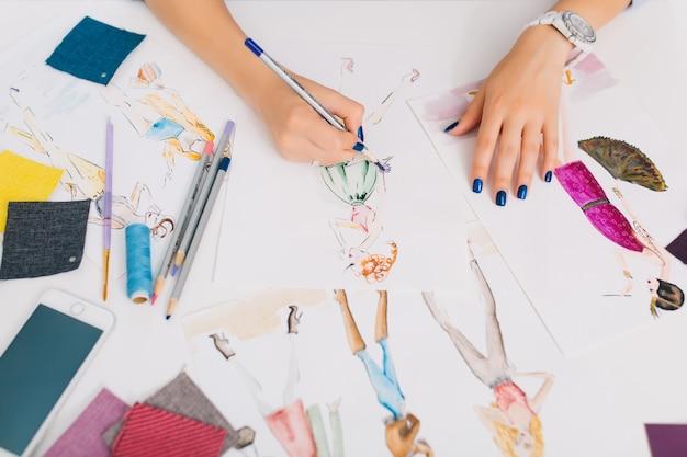 Esta imagem descreve os processos de criação de roupas. há mãos de uma garota desenhando esboços sobre a mesa. há uma confusão criativa com coisas diferentes na mesa.