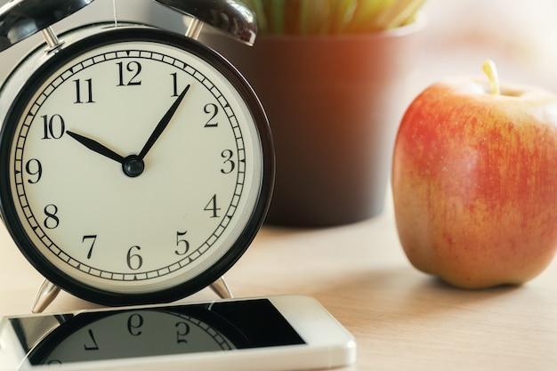 Está na hora da escola. despertador vintage e apple na mesa de madeira