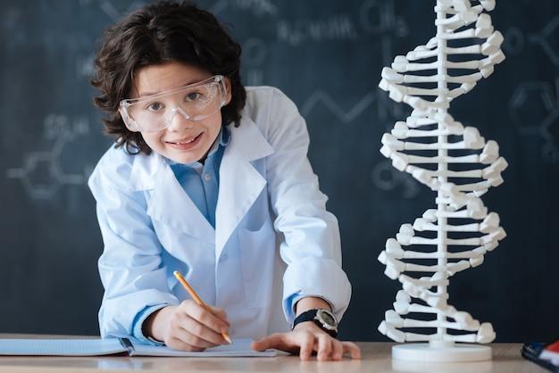 Estabelecendo um padrão na educação. aluno inteligente feliz e bem-sucedido em pé no laboratório e fazendo anotações enquanto estuda ciências e trabalha no projeto