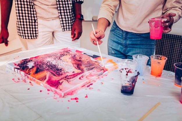 Estaca de madeira. close de uma talentosa artista segurando um pedaço de madeira enquanto pinta