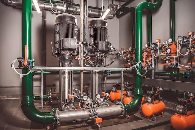 Estação de bomba de água e tubulação com tanques em uma sala industrial para fornecer água de alta pressão para tarefas de combate a incêndios
