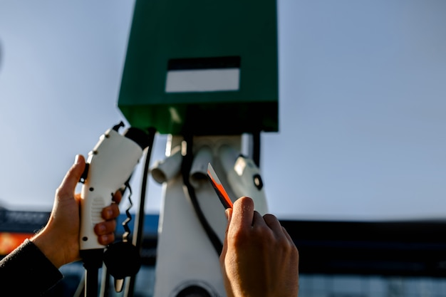 Estação de carregamento para veículo elétrico. close-up do carregador e cartão de crédito