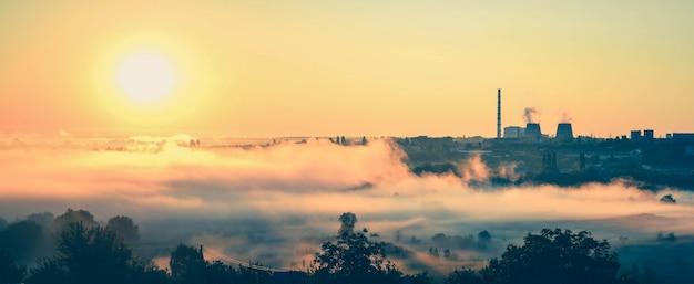 Estação de energia panorâmica e o amanhecer com névoa