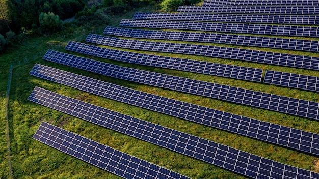 Estação de energia solar em campo verde em dia ensolarado. vista aérea. suportes para painéis solares