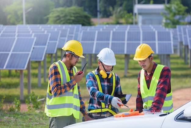 Estação de energia solar, painéis solares com técnico, produção elétrica do futuro, engenheiros asiáticos