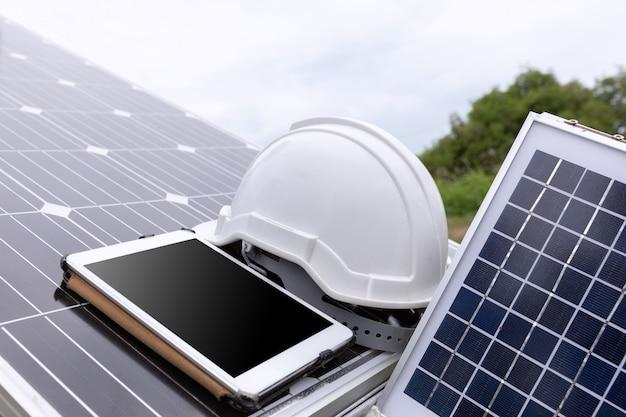 Estação de painéis solares fotovoltaicos verifica com computador tablet.