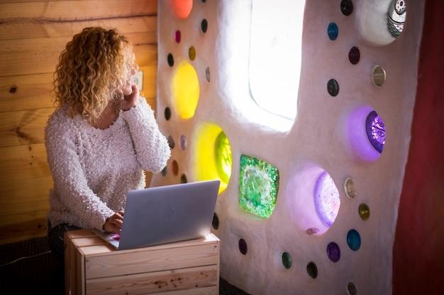 Estação de trabalho alternativa em casa ou escritório para uma jovem mulher bonita e encaracolada sentada no chão trabalhando em um laptop, olhando pela janela