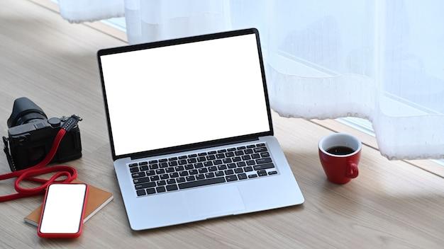 Estação de trabalho do fotógrafo ou designer com laptop de tela em branco branca, câmera, celular e xícara de café no chão.