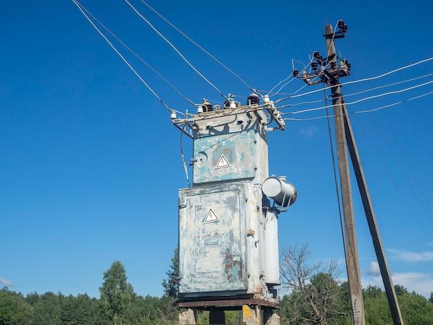 Estação de transformador velha e enferrujada no verão em um dia claro contra o céu azul