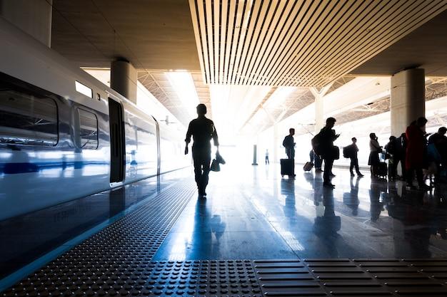 Estação ferroviária coberta com trens e silhuetas de pessoas correndo