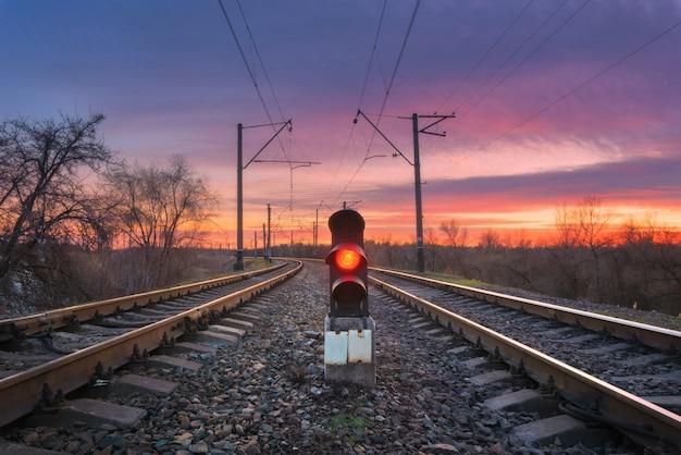 Estação ferroviária com semáforo contra lindo céu ao pôr do sol