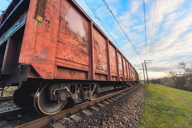 Estação ferroviária com vagões de carga e trem ao pôr do sol