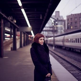 Estação ferroviária. linda garota está de pé na plataforma e esperando o trem