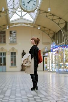 Estação ferroviária. linda garota está esperando o trem. mulher viaja luz
