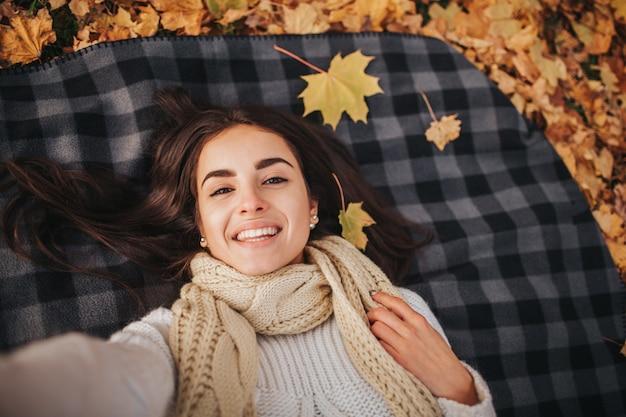 Estação, tecnologia e conceito dos povos - jovem mulher bonita que encontra-se na terra e nas folhas de outono e que toma o selfie com smartphone