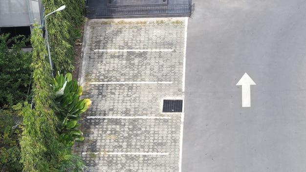 Estacionamento ao ar livre e linha branca de concreto e seta branca e árvore.