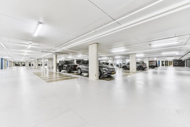 Estacionamento coberto de prédio de apartamentos subterrâneo com piso branco e automóveis estacionados em filas