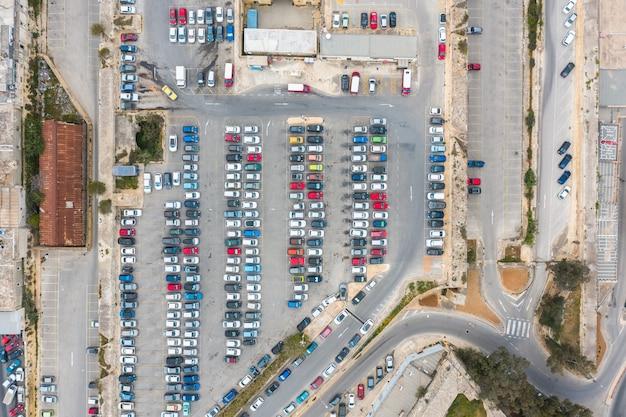 Estacionamento de carros e ônibus, com vias e parada na cidade, vista aérea de cima.