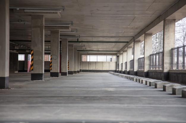 Estacionamento de vários níveis com marcações claras durante o dia com vagas vazias, com colunas e ladrilhos