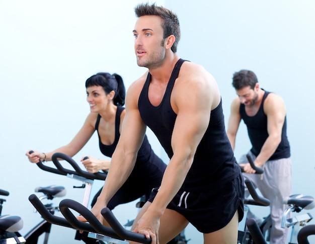 Estacionária fiação bicicletas fitness homem em um clube de esporte de ginásio