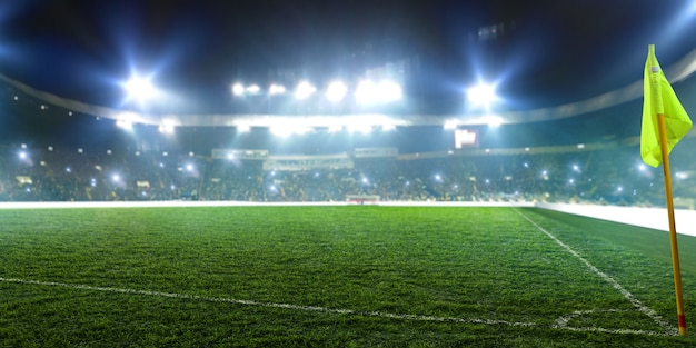 Estádio de futebol, bandeira de canto, luzes brilhantes, vista da grama do campo. relvado, ninguém no parquinho, tribunas com ventiladores no fundo