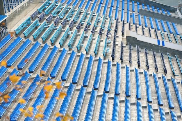 Estádio de futebol com fileiras de assentos azuis vazios
