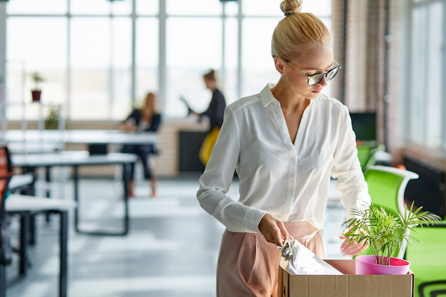 Estagiária caucasiana segurando uma caixa de papelão com pertences iniciar ou terminar o trabalho na empresa